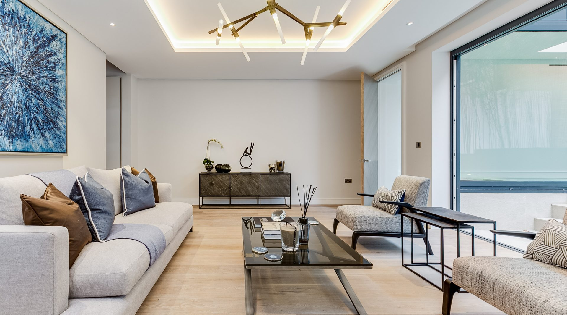 """A completely new built five-bedroom townhouse, which enjoys East to West facing light situated on just off Kensington High Street, a moments' walk from Holland Park, Kensington Gardens and Hyde Park. Onyx London were enlisted to complete the interior design of this luxury property in a way that would be harmonious with the affluence of the surrounding Kensington area. The townhouse is arranged over six floors and has been built to an extremely high standard offering luxurious accommodation over 6,600 sq. ft. The ground floor has a large entrance, which leads into the formal reception overlooking the garden, with a study area above on the first floor. The upper basement level comprises a huge open plan kitchen, dining and family area with a feature floating staircase leading up to the formal reception. Italian kitchen in a bespoke Bolivar Veneer, Bronze metallic and an island in Grey Marquina marble, fully fitted with Gaggenau appliances. Leading off the main staircase lobby, is a media room wired for a State-of-the-art Cinema system with bespoke walnut and acoustic panelled joinery designed for an 85"""" 4K screen and surround sound and is wired for Crestron system installation that can control through Crestron touchscreens and iPad minis. The smart home technology was designed and installed by SMC an award-winning system integrator. The lighting design was completed by London Lightworks and the cutting-edge lighting dimming system was from Lutron. The middle basement level hosts a large swimming pool with an entertainment area, jacuzzi, steam room, spa change and gym. The master suite is on the first floor with a walk-in wardrobe in a bespoke Bolivar veneer and fabric panelled joinery, with his and hers drawer units, hanging rails and a dressing table. The master en suite boasts a large shower, bath and double vanity basin, in a beautifully golden veined Sivec Marble. The second and third floor comprises four further guest bedrooms, with bespoke wardrobes and well-des"""